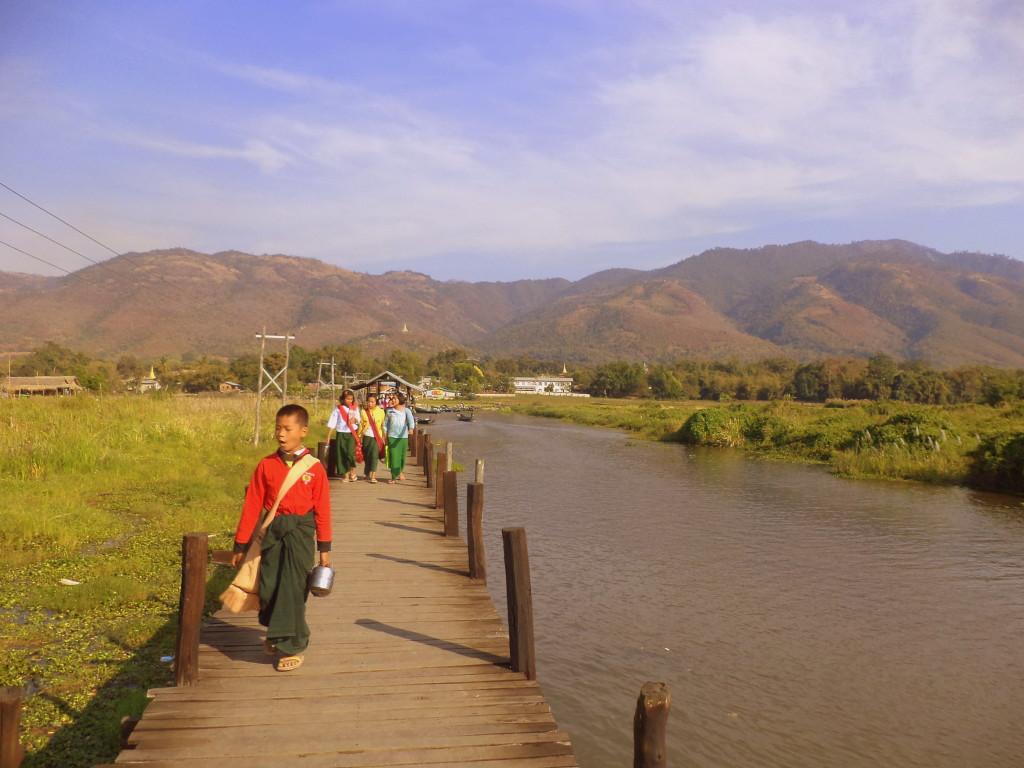 Niño con uniforme escolar compuesto por longyi. A todo esto, carga el típico termo de metal: ¡Todo un clásico en las alacenas birmanas! Lago Inle.