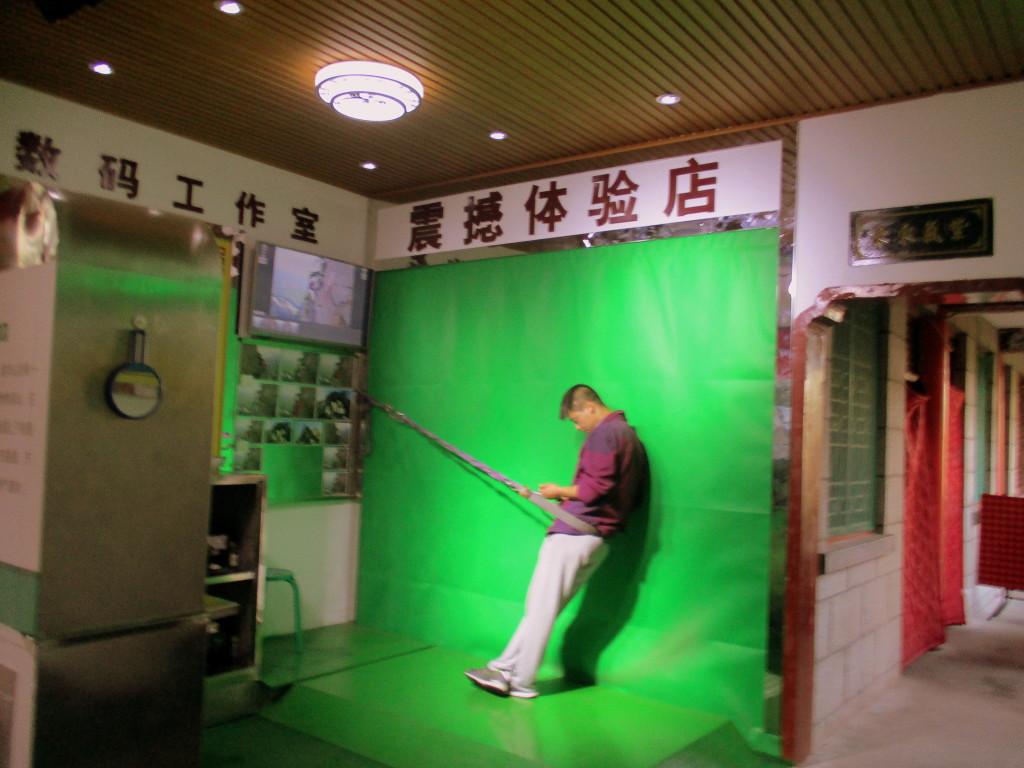 En caso de que no se animen, afuera del Plank in the Sky está este mae con un puestillo y un telón verde como los que usan en los efectos especiales de las películas para tomar la foto falsa de haber estado caminando por ahí. He aquí el mae que la administra jugando con el celular en su tiempo libre. Recordemos: esto aquí tiene sentido. En China la imagen es TODO.