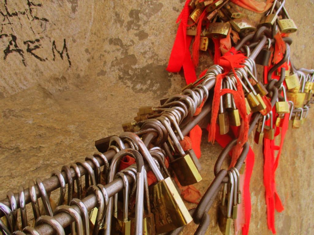"""En el monte HuaShan la decoración por antonomasia son los candaditos del amor y los lazos rojos. Están por toooodas partes, incluyendo las cadenas de las que uno se tiene que agarrar al caminar en la tabla porque, ¿qué importa la seguridad cuando se ve """"bonito""""? Como les digo: antes muertos que sencillos."""