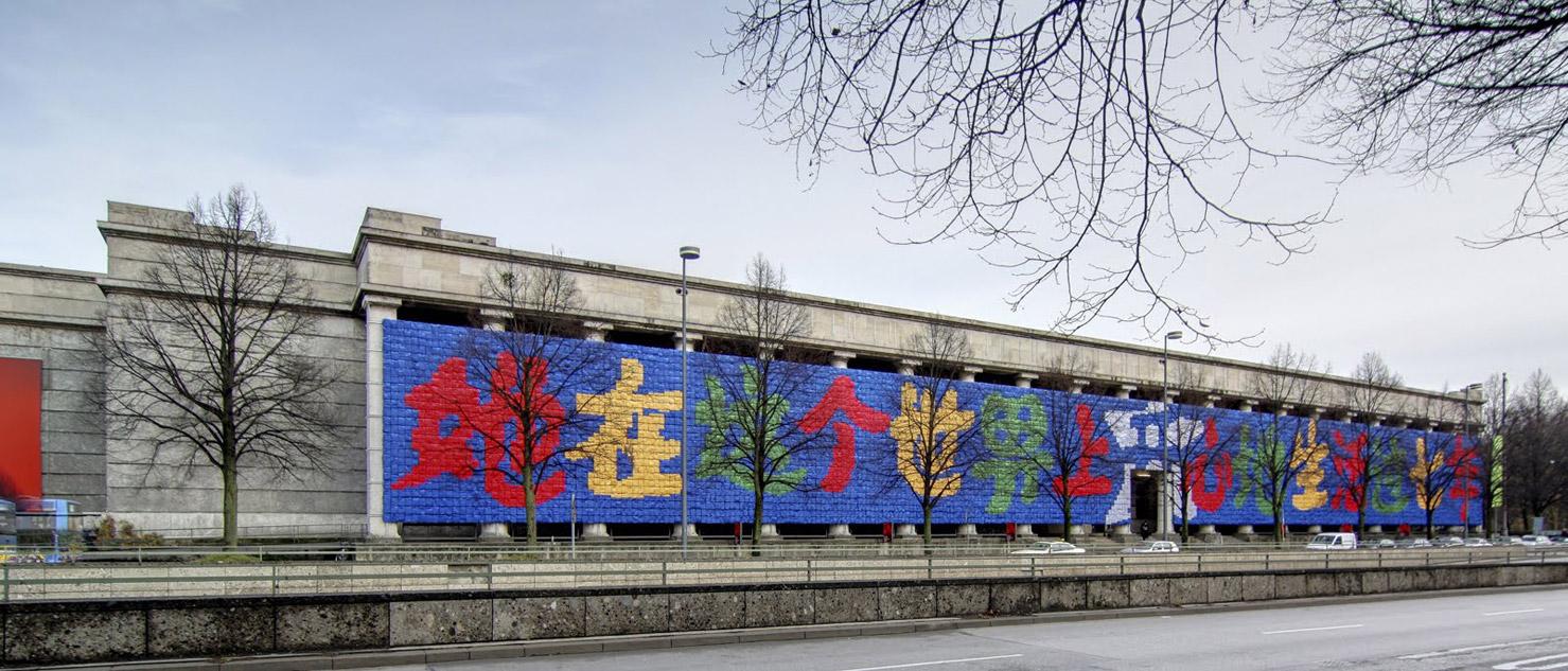 """""""Ella vivió felizmente por 7 años en este mundo"""". Eso dice en chino escrito con 9 mil mochilas escolares en la fachada de este edificio. La frase es de la madre de una niña de 7 años que murió en una escuela tofu durante el terremoto de 2008. Es parte de la presentación """"Recordando"""" montada en Munich, Alemania por el artista chino Ai Weiwei. Ai Weiwei es un artista plástico reconocido a nivel mundial y quien ha luchado incansablemente porque llevar a quienes construyeron esas escuelas de forma corrupta ante la justicia. Asimismo, es uno de los opositores más acérrimos del gobierno de su país y, posiblemente, el chino más activo en Twitter. Su investigación acerca de las escuelas lo llevó a convertirse en un """"desparecido"""" del gobierno chino luego de ser arrestado. Por una enorme presión dela comunidad artística internacional, fue liberado después de un tiempo. Sin embargo, su taller fue destruido en Beijing."""